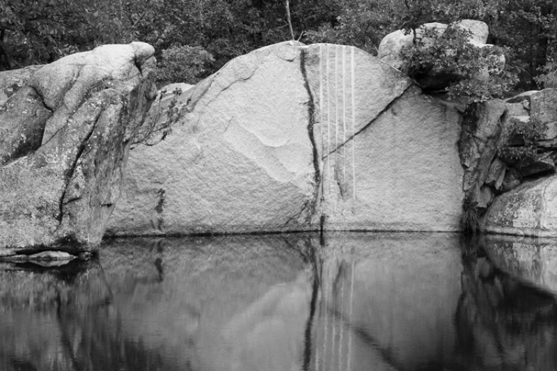 Rock Face And Reflections In A Granite Quarry