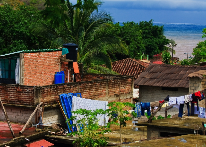 Small Village With Banderas Bay In Background
