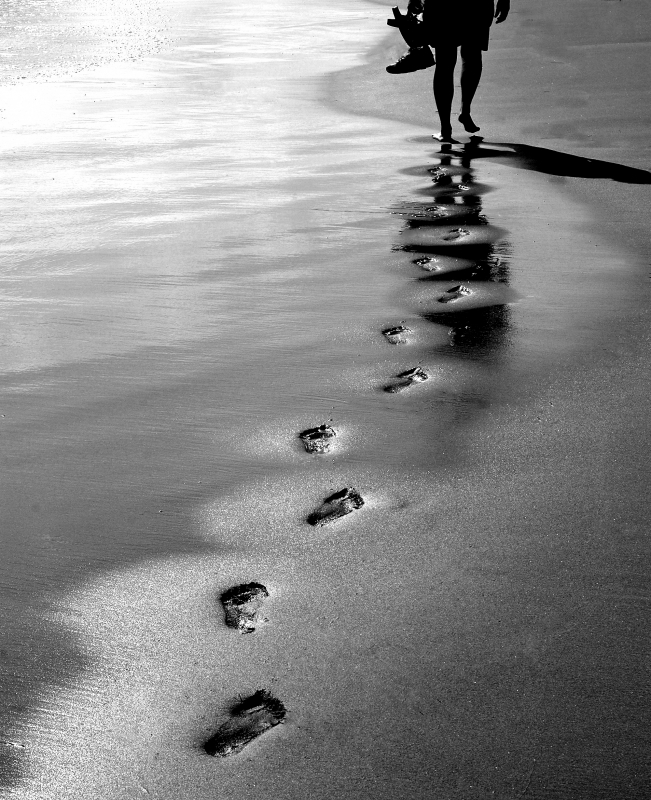 Pensive Footsteps On The Beach