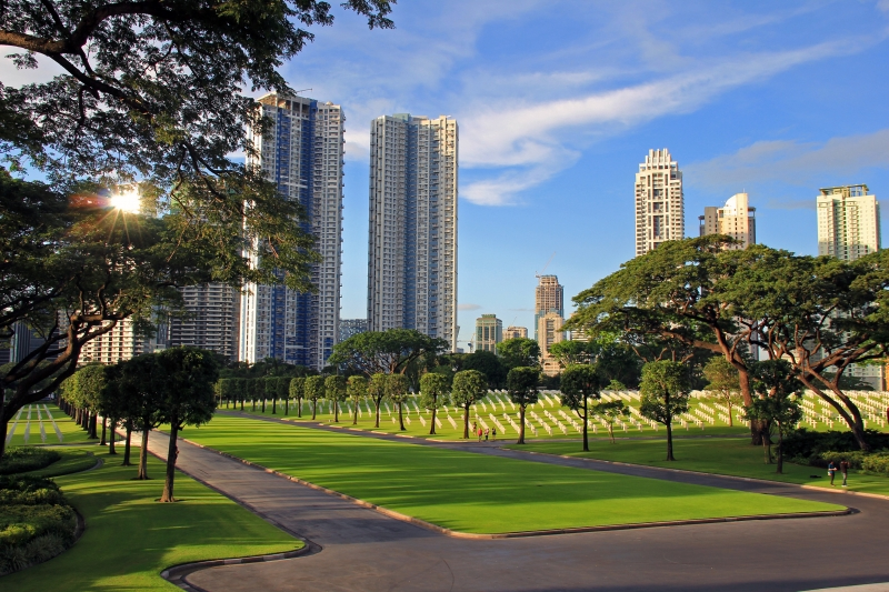 Sun Reflecting Off The Taguig City Skyline Overlooking The Manila American Cemetery And Memorial