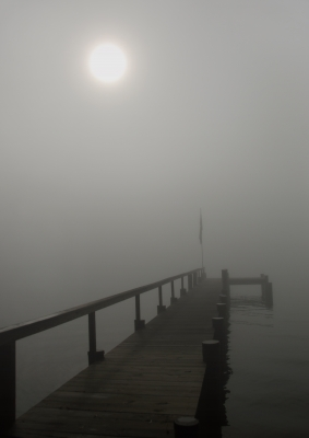 Sun Peaking Through Fog Over Pier