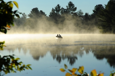Couple Fishing In Rowboat In Early Morning Mist