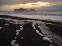 Sea Foam On Rialto Beach With Lapush Sea Stacks In The Distance.