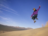 Woman Leaping Off Sand Dune