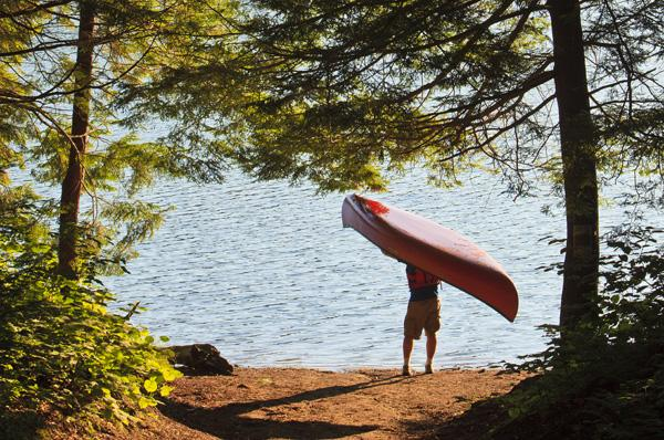 A man next to his canoe at Zack Woods Pond, Hyde Park, Vermont.  Early morning.