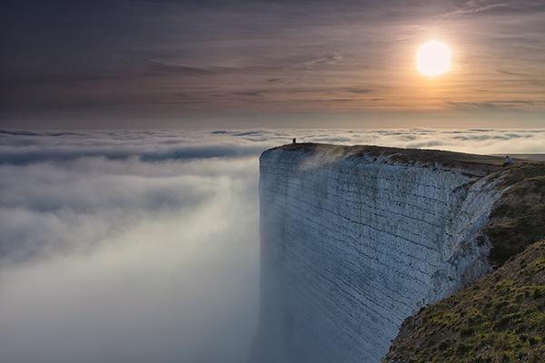 Fog rolling over a cliff chalk headland in East Sussex Southern England with tourists for scale