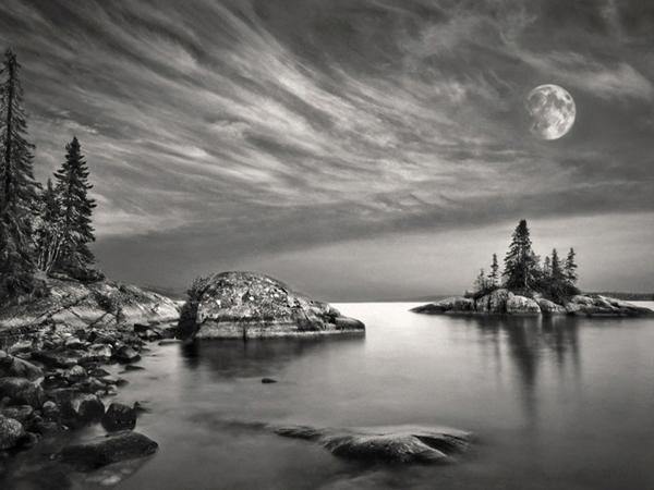 Black and white double exposure of moon and landscape along the Great Lakes Lake Superior in Ontario Canada