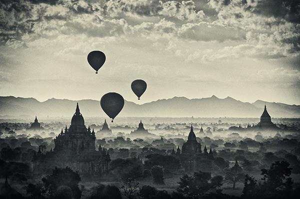 Black and white toned Three hot air balloons flying above temples with clouds in Bagan in Burma Myanmar