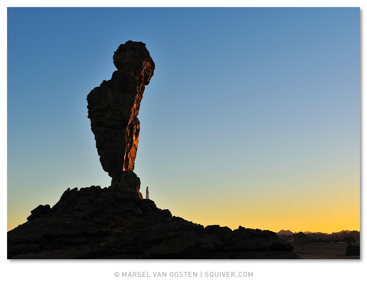 Marsel van Oosten, Marsel, Squiver Tuareg standing next to gigantic natural rock monolith at sunset. Acacus region, Libya.