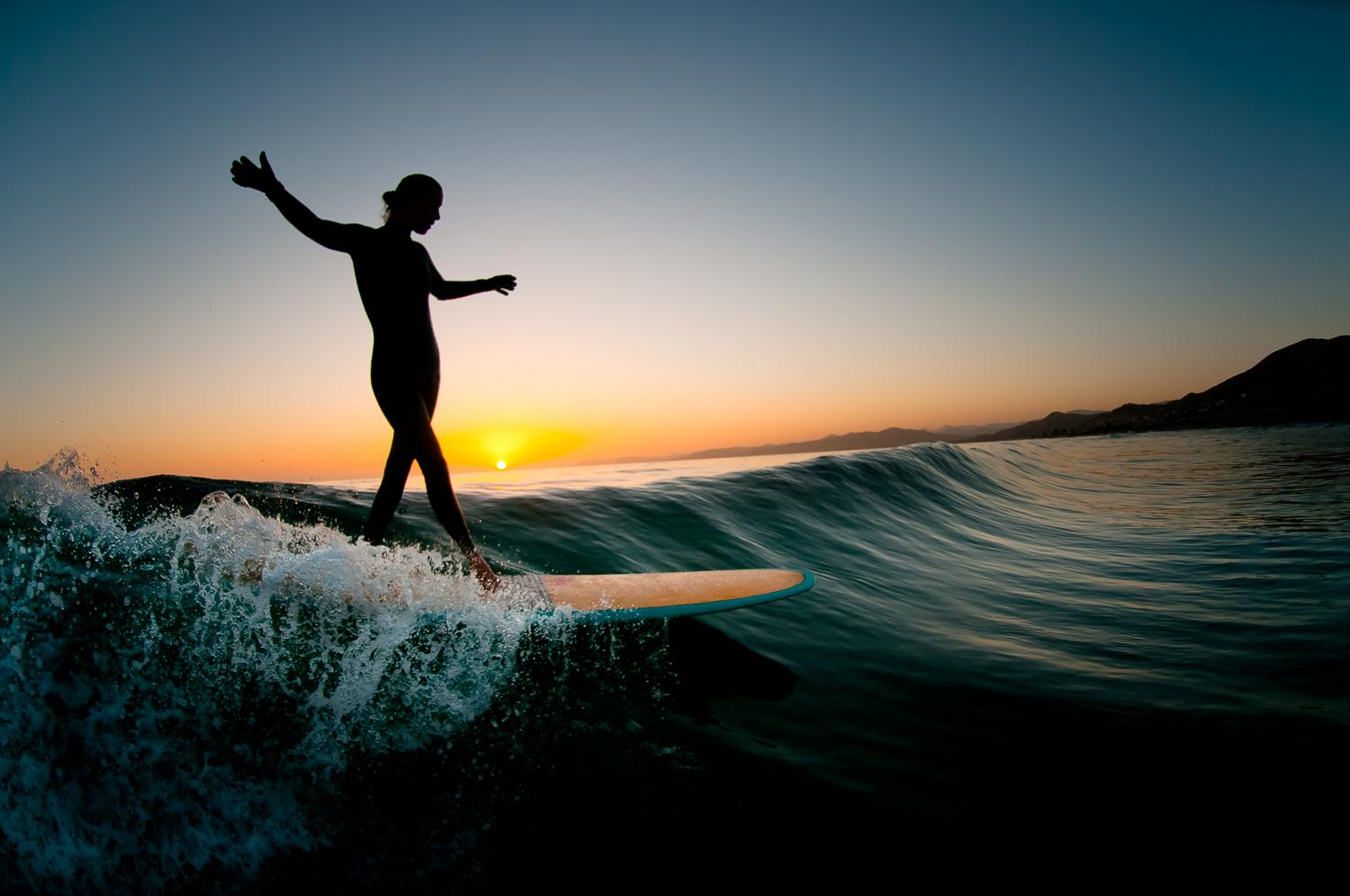 Crystal Thornburg catches a wave in the Big Sur surf in surfing photos from Central California silhouette pose sunset