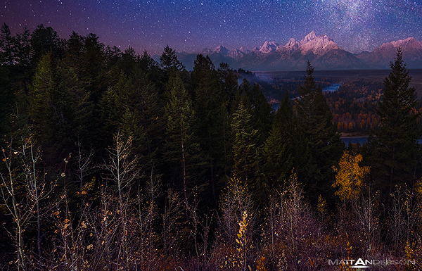 This is a multiple exposure of the Grand Tetons with a pre-dawn glow, light painting, and the Milky Way above. A long exposure for the sky and stars, a second exposure with light painting, and a third exposure of the first light bathing the Moutain tops. All taken hours apart. Below you can see the snake river twisting through the scene. Some distant smoke and fog layers the hillside and mountain bases.