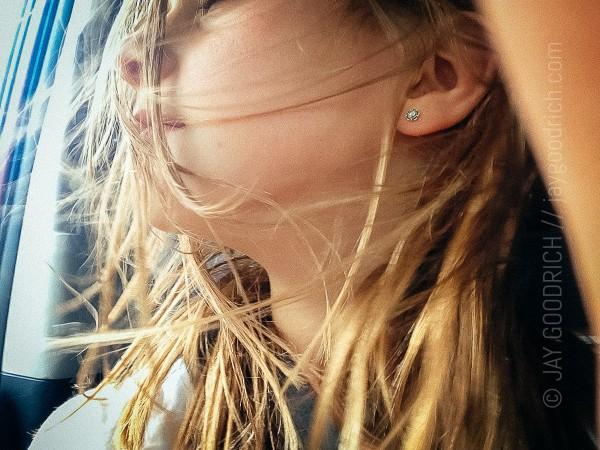 Jade Goodrich has her hair blowing in the truck while heading to mountain bike with her father at Jackson Hole Mountain Resort, Wyoming.