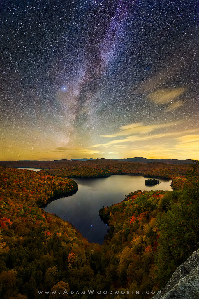 """Autumn Milky Way Over Nichols Pond Vermont I recently spent a few days in Vermont with Michael Blanchette and Benjamin Williamson, chasing the amazing fall colors all over the place. The foliage was at peak color in many places and looked amazing! Nikon D810A and Nikon 14-24mm f/2.8 lens, at f/2.8 and 14mm. This is a blend of 10 images for the sky and 2 images for the foreground. The 10 images were shot at ISO 10,000 for 10 seconds each and stacked with Starry Landscape Stacker to produce a result with pinpoint stars and low noise. A single foreground shot at ISO 1600 for 15 minutes was used to capture detail in the foliage and mountains, and another shot at ISO 12,800 for 25 seconds (a """"backup"""" shot for my sky in case the star stacking doesn't work out) was used for the reflection in the lake. The 25 second shot had a good reflection in the lake (as good as you could get with the wind) so I used just the lake from that shot."""