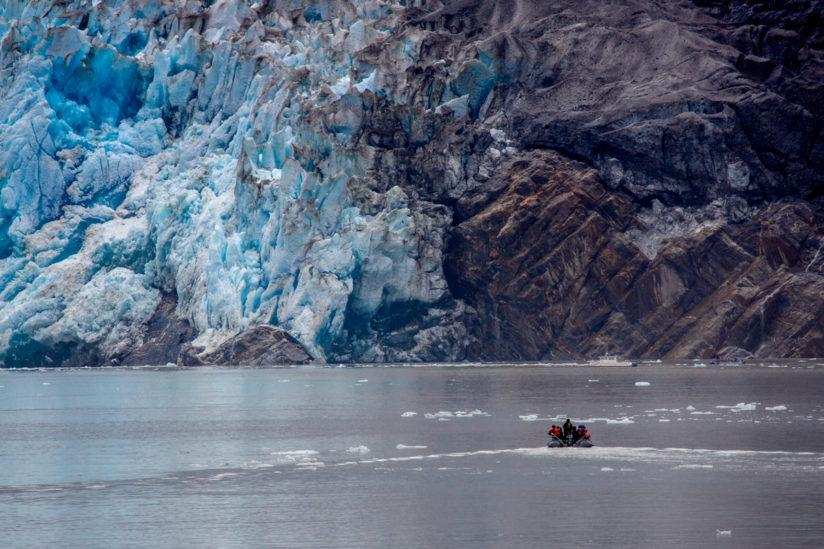A boat approaches the end of a glacier.