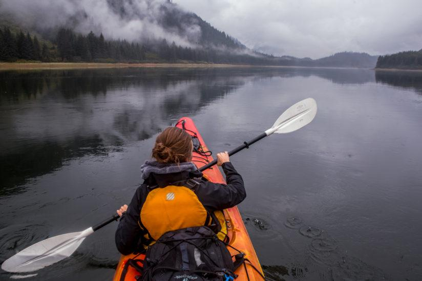 A woman kayaking in the Fjords of South Eastern Alaska.