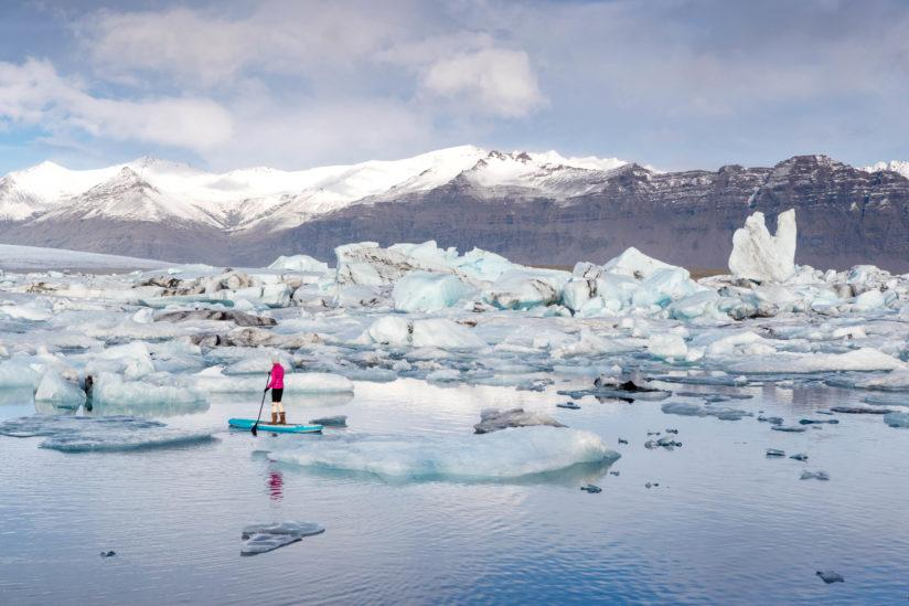 Amber Arbucci paddle boarding in a glacial lagoon.