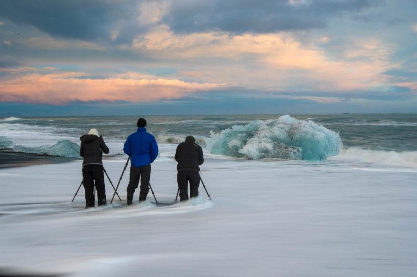 Photographer photographing an iceberg on diamond beach.